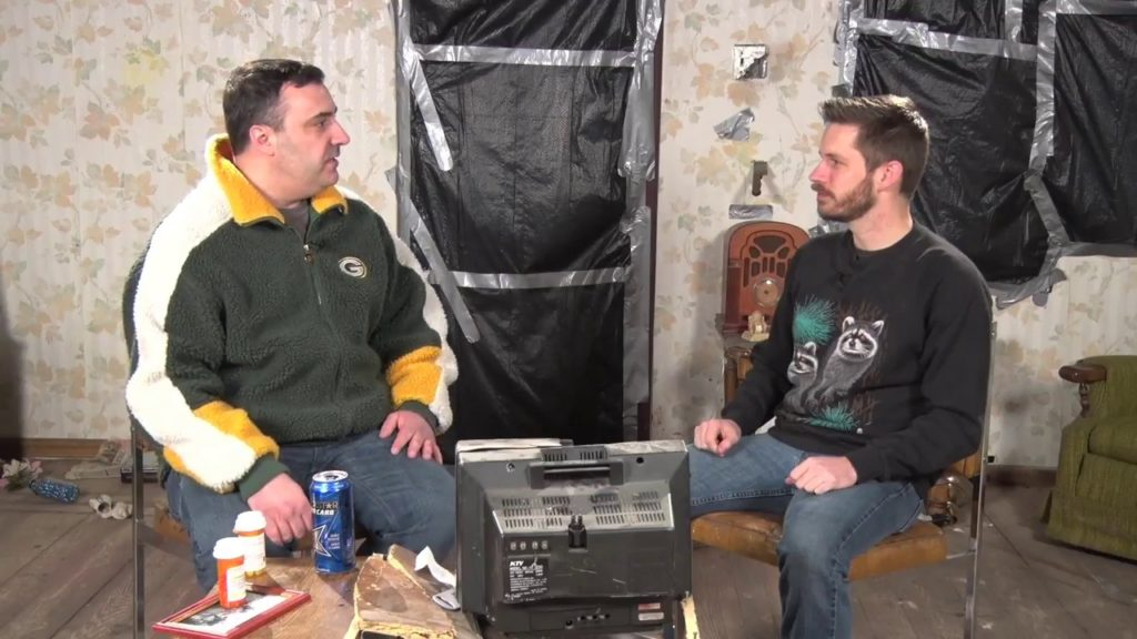 Two habitual drunk men sit on a trashed set with garbage bags hanging on the walls